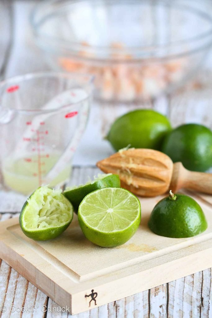 Cut limes and a juicer on a small wooden cutting board.