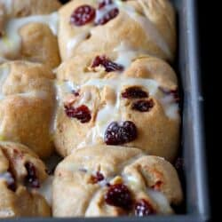 This healthy whole wheat hot cross bun recipe is perfect for Easter breakfast. The tart cherries and lemon glaze add a sweet tang to the tender buns. #hotcrossbuns #Easter #recipe
