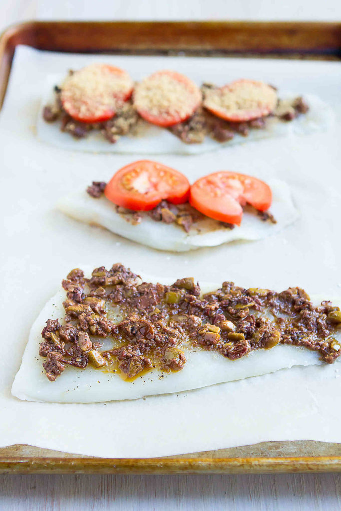Cod fillets on a parchment-covered baking sheet, each topped with olive tapenade, tomatoes and breadcrumbs.