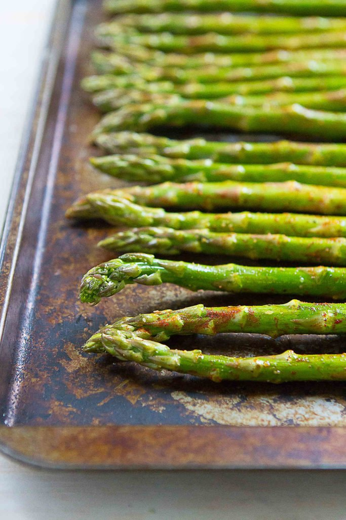 Asparagus spears, tossed in olive oil and seasoned with smoked paprika, lined up on a baking sheet.