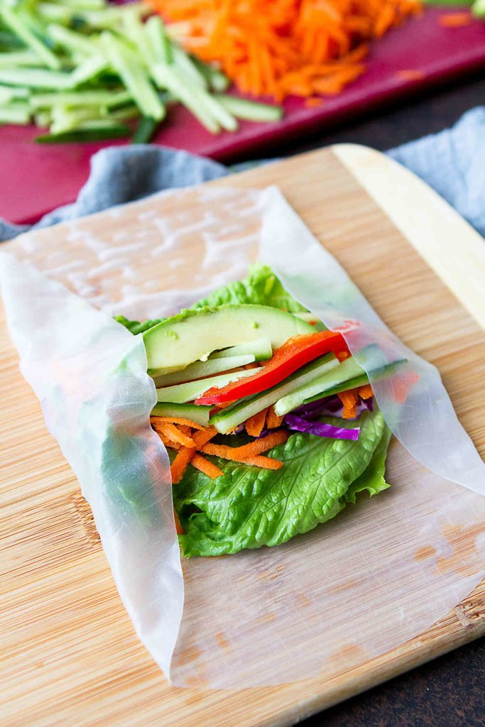 Avocado, lettuce, carrots and cabbage on a spring roll wrapper, with edges folded in.
