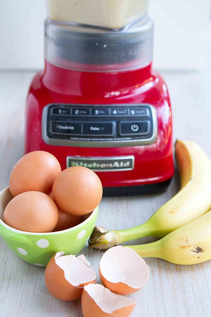 Bananas, eggs in a green bowl and a blender on a white background.