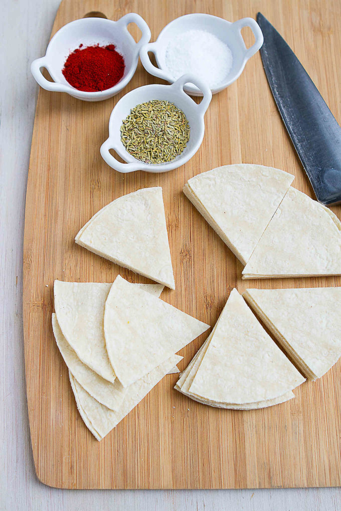Corn tortillas, cut into triangles, on a cutting board with bowls of spices.