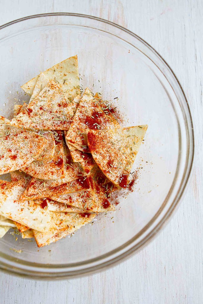 Tortilla triangles in a glass bowl, sprinkled with salt, smoked paprika and rosemary.
