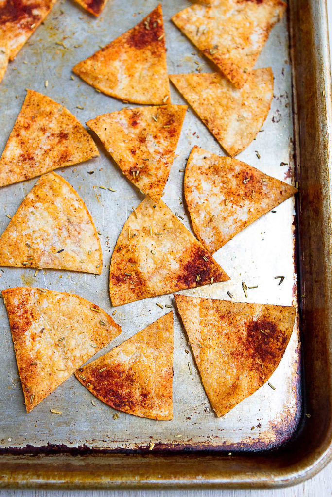 Baked corn tortilla chips are spiced up with smoked paprika and rosemary. Perfect for dipping in hummus! 78 calories and 2 Weight Watchers Freestyle SP #tortillachips #recipe #glutenfree