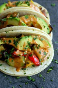 Grilled vegetable tacos (vegan and gluten free) are completely irresistible and satisfying when tossed in a light peanut sauce and topped with avocado slices. 238 calories and 6 Weight Watchers Freestyle SP #tacos #vegan #glutenfree #weightwatchers