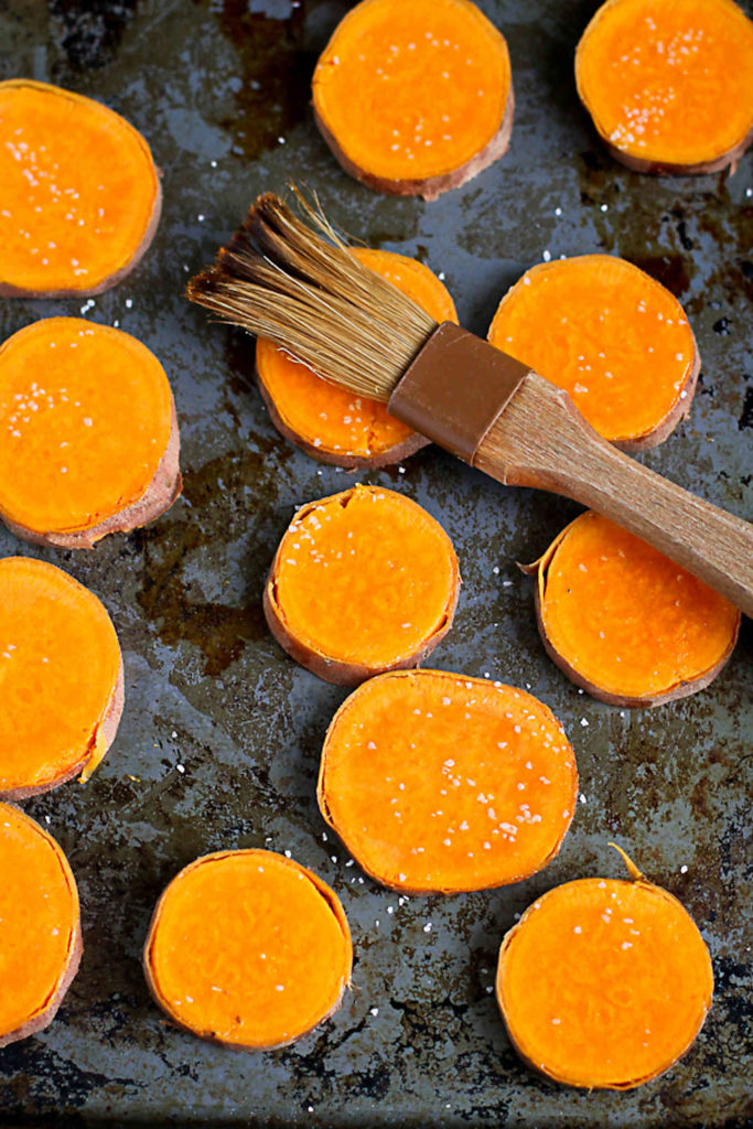Sweet potato slices on a baking sheet, brushed with olive oil.
