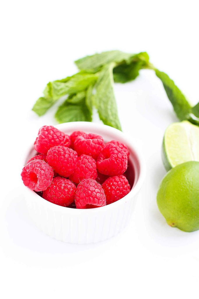 Raspberries in a bowl, with fresh limes and mint springs.