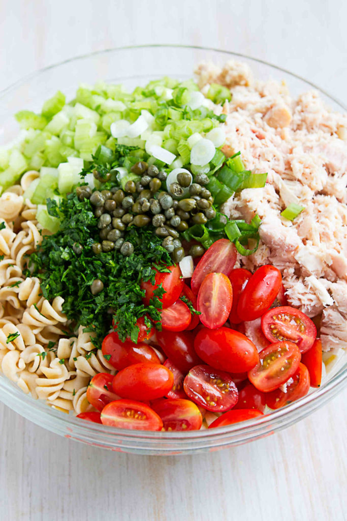 Whole wheat pasta, tuna, tomatoes, celery, capers, parsley and green onions in a large glass bowl.
