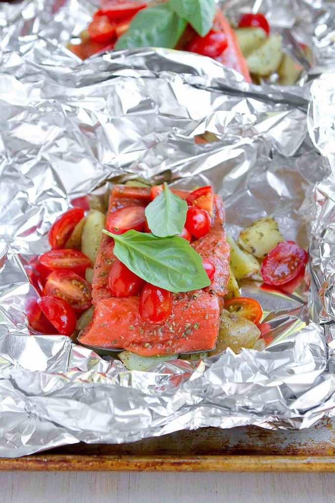 Salmon, potatoes, grape tomatoes and basil in a foil packet, ready to cook.