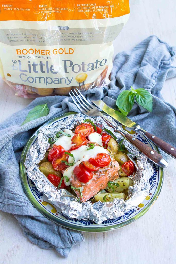 All the flavors of caprese salad come together in this salmon and potato meal, cooked in foil packets. 404 calories and 7 Weight Watchers Freestyle SP #wwfreestyle #healthydinnerrecipes #grilling