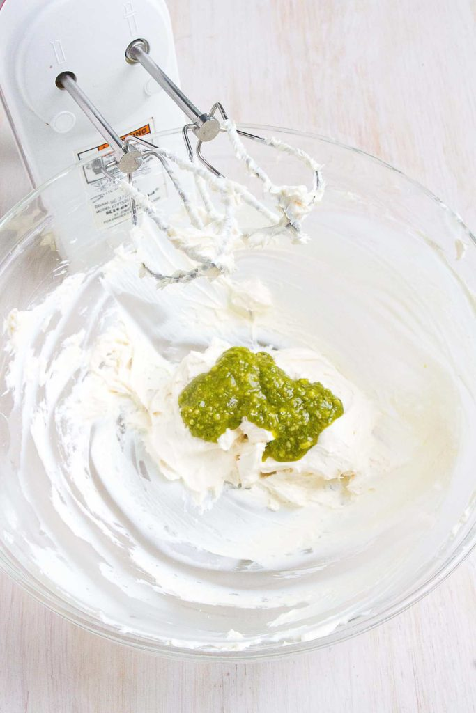Pesto and Neufchatel cheese in a glass bowl with a hand mixer.