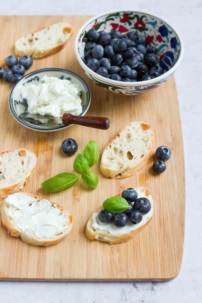 Crostini, spread with goat cheese and topped with blueberries and basil, on a bamboo cutting board.
