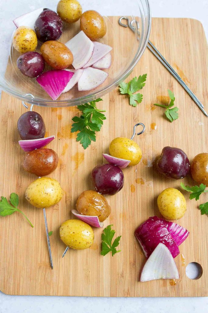 Potato and onion skewers, plus springs of parsley, on a bamboo cutting board.