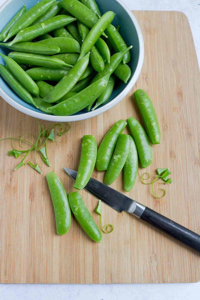 Destringing sugar snap peas on a wooden cutting board.
