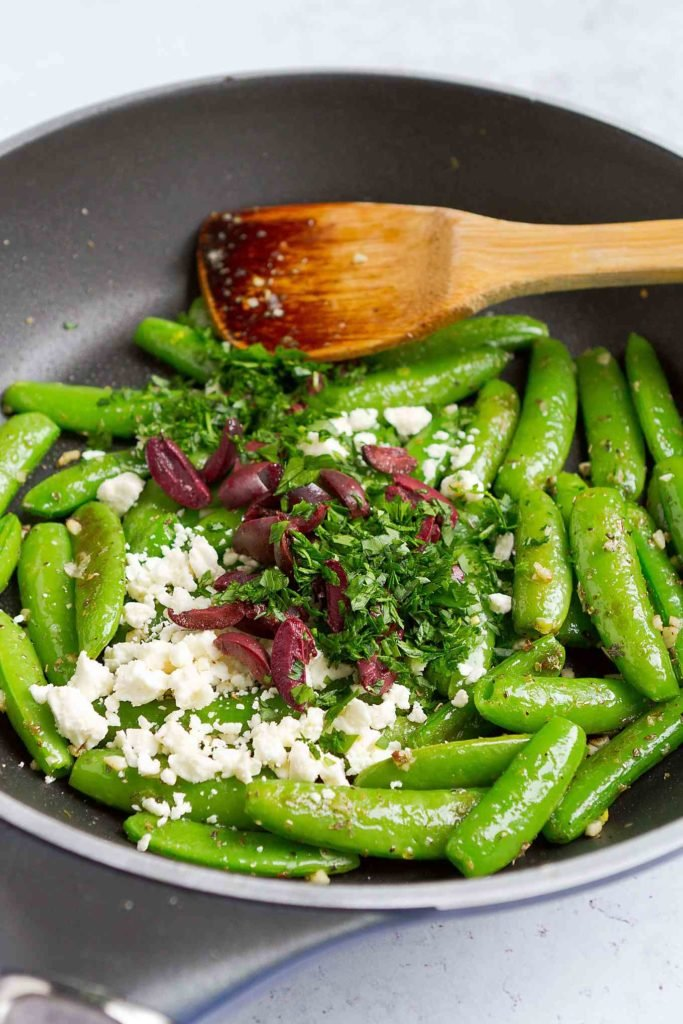 Sugar snap peas in a large nonstick skillet, with feta cheese, kalamata olives and parsley.