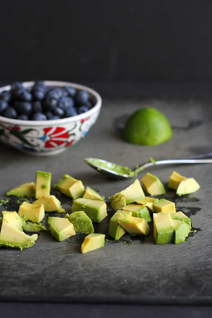 Chopped avocado, a bowl of blueberries and a lime half on a black cutting board.