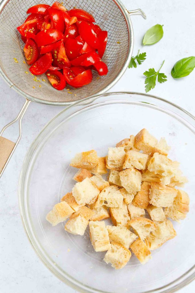 Toasted bread cubes in a glass bowl and chopped tomatoes in a sieve.