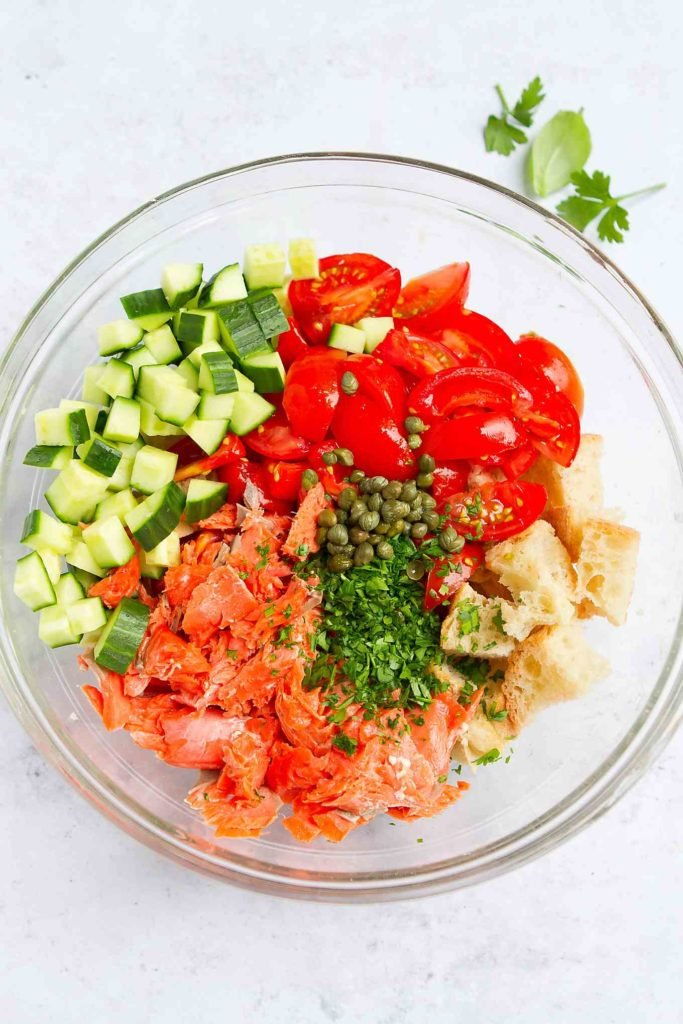 Salmon, bread cubes, tomatoes, cucumber and parsley in a large glass bowl.