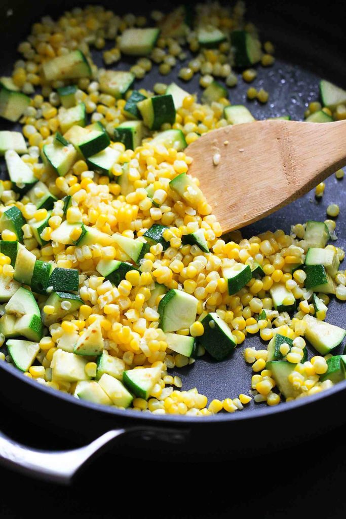 Cooking zucchini and fresh corn in a large nonstick skillet.