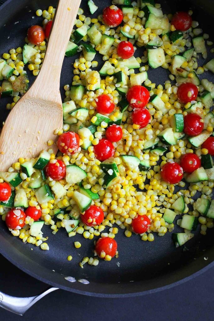 Zucchini, corn and cherry tomatoes in a large skillet. Stirring with a wooden spatula.