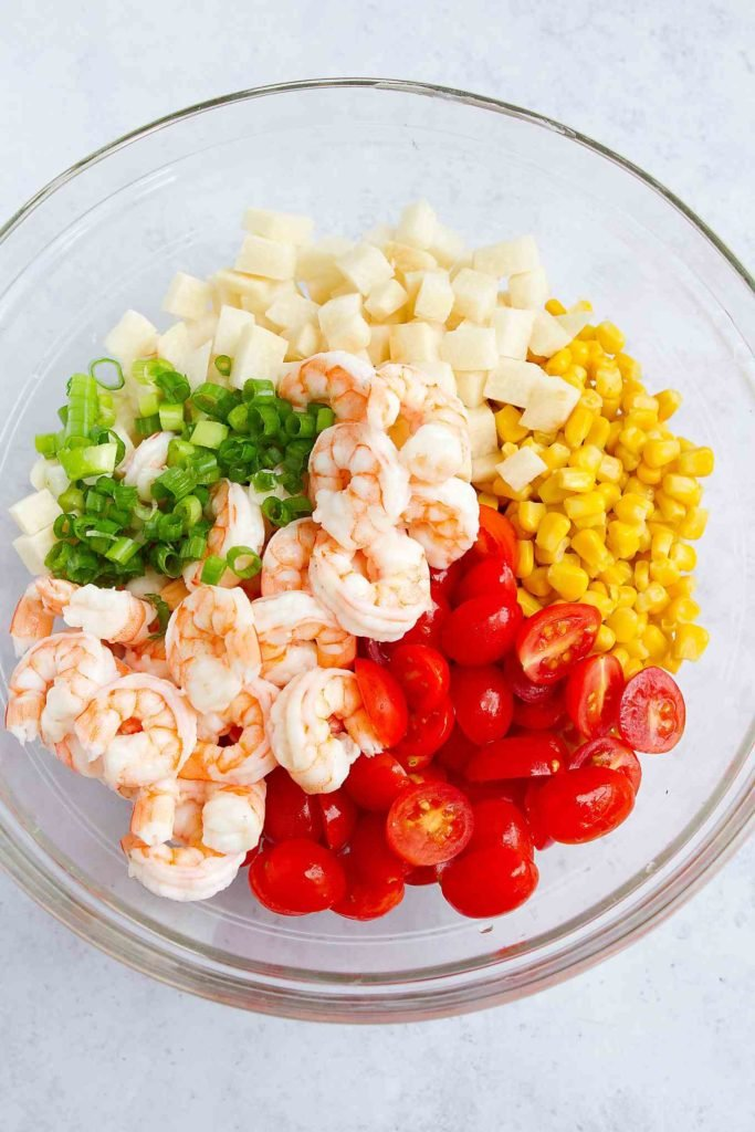 Cooked shrimp, grape tomatoes, corn, jicama and green onions in a glass bowl.