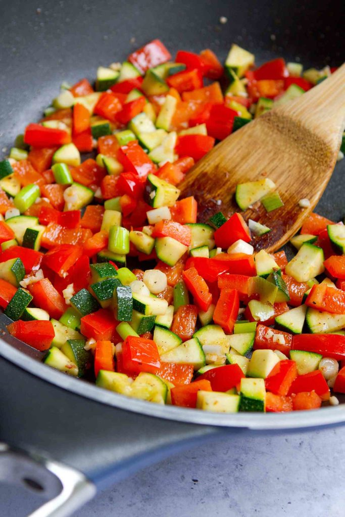 Diced zucchini and red bell peppers in a nonstick skillet.