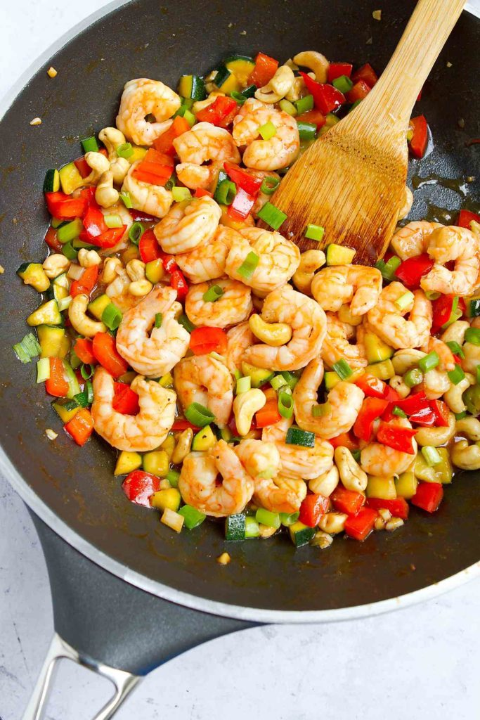 Stir fried shrimp, bell peppers and zucchini in a large skillet.
