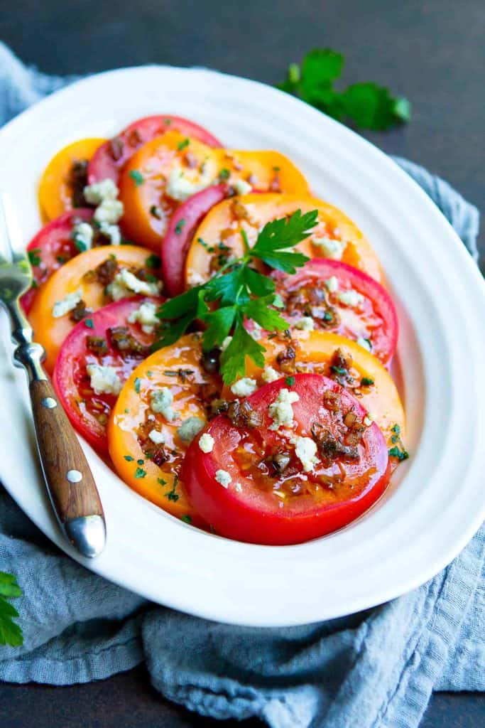Summertime tomatoes are fantastic on their own, but this Heirloom Tomato Salad is taken to the next level with a light vinaigrette and blue cheese crumbles. 86 calories and 3 Weight Watchers Freestyle SP #tomato #saladrecipes #healthy