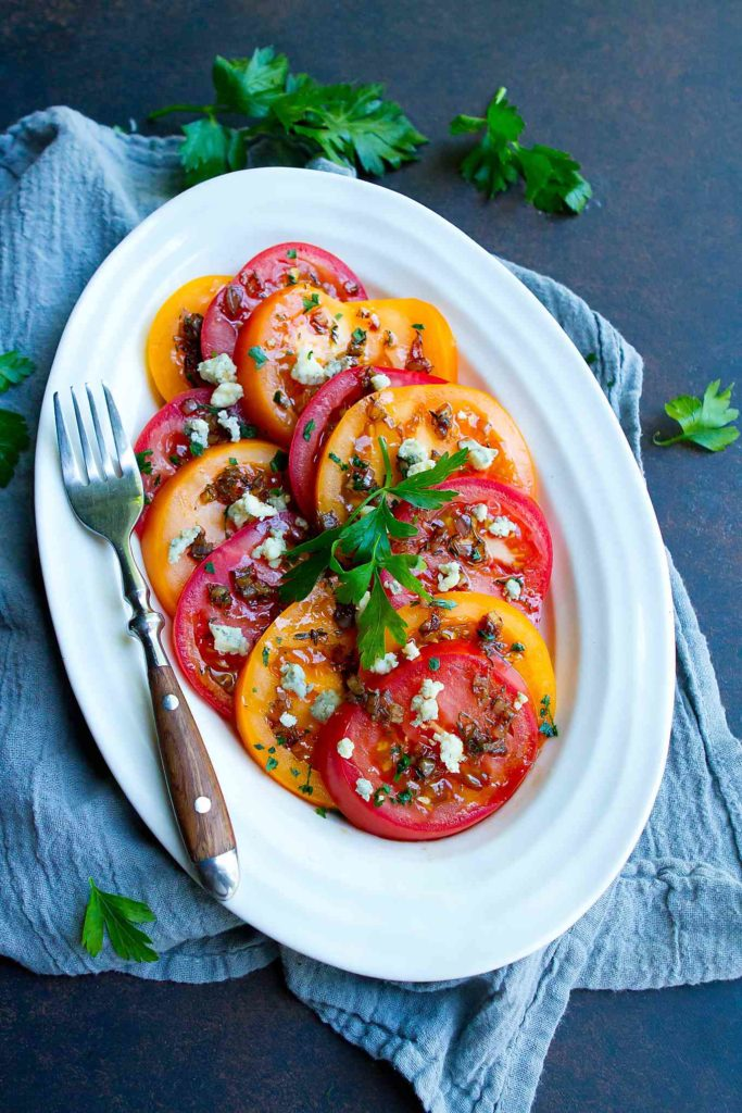 This sliced tomato salad is drizzled with an easy shallot balsamic vinaigrette. The perfect balance of sweet and savory! 86 calories and 3 Weight Watchers Freestyle SP #tomatoes #healthyrecipes #sidedish