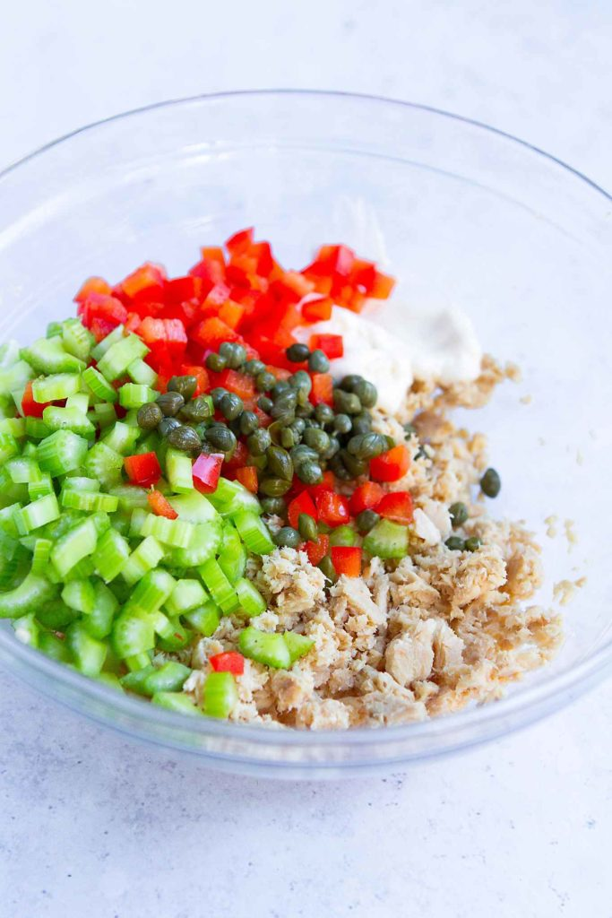 Salmon, diced celery, diced bell pepper, capers and mayonnaise in a glass bowl.