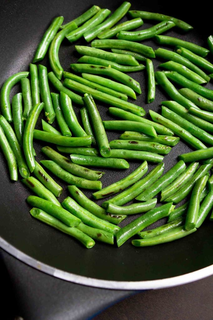 Green beans in a nonstick skillet.