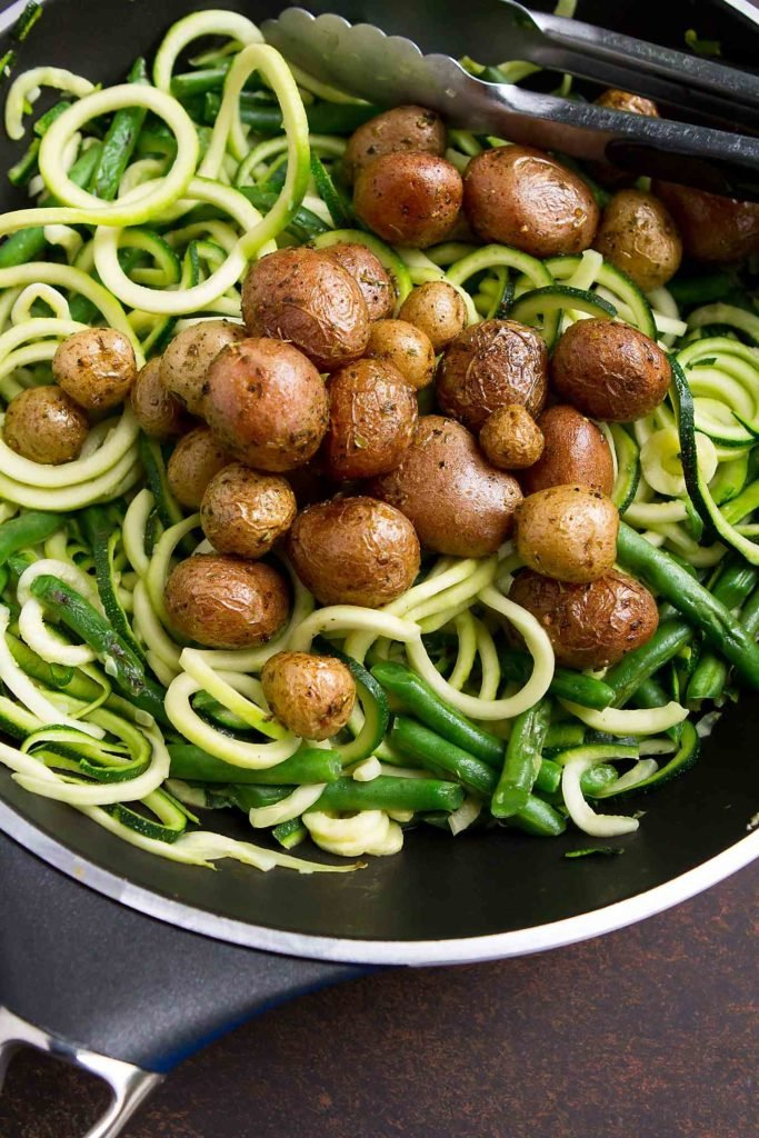 Zucchini noodles, green beans and little potatoes in a nonstick skillet.