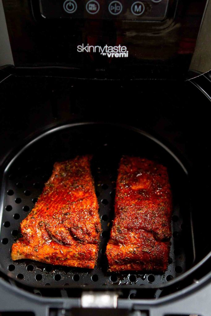 Cooked spice crusted salmon in the basket of an air fryer.