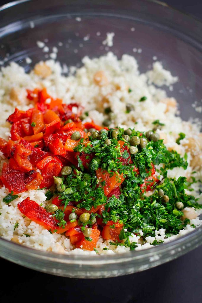 Cauliflower, roasted peppers, parsley and capers in a glass bowl.