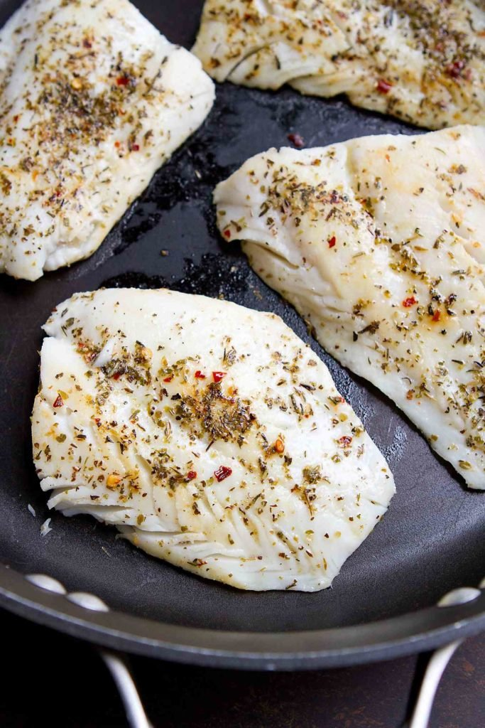 Seared herb-crusted cod fillets in a nonstick skillet.