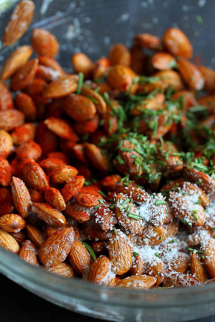 Raw almonds, smoked paprika, kosher salt and rosemary in a glass bowl.