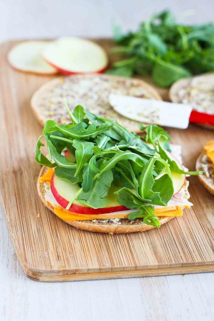 Sandwich rounds topped with turkey, apple, cheddar and arugula.