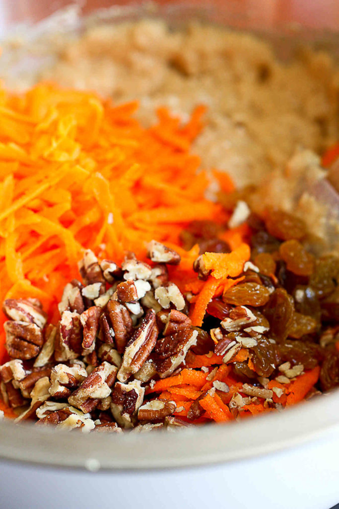 Grated carrots, pecans and muffin batter in a mixing bowl.