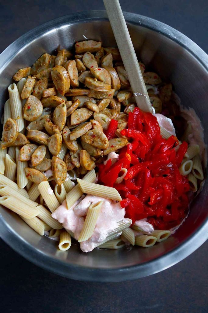 Cooked pasta, sausage and roasted peppers in a large mixing bowl.