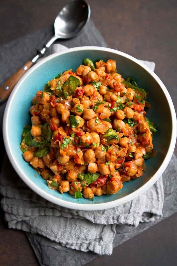 This Crockpot Spiced Chickpea Stew (Vegan) is one of the first meatless meals I fell in love with. So much flavor and your kitchen will smell amazing! 295 calories and 1 Weight Watchers SP | Vegetarian | Slow Cooker | Mediterranean | Easy | Dinner | Healthy | Spinach #cookincanuck #veganrecipes #crockpotrecipes