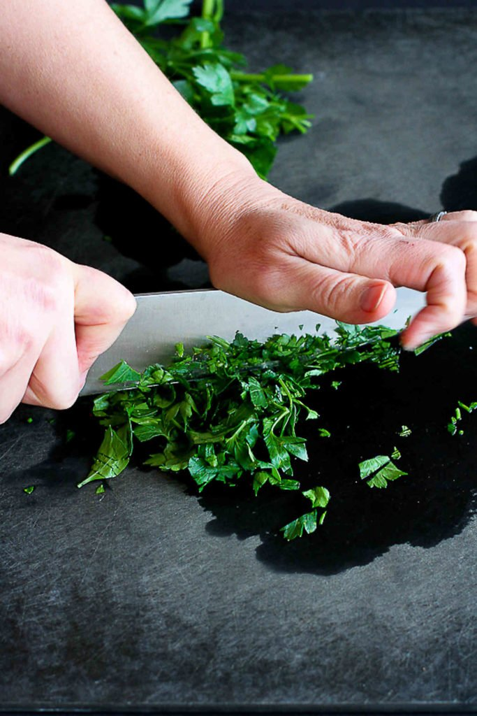 Chopping parsley on a black cutting board, using a chef's knife.