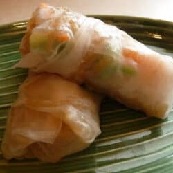 Spring roll wrappers filled with noodles and other ingredients. On a green plate.