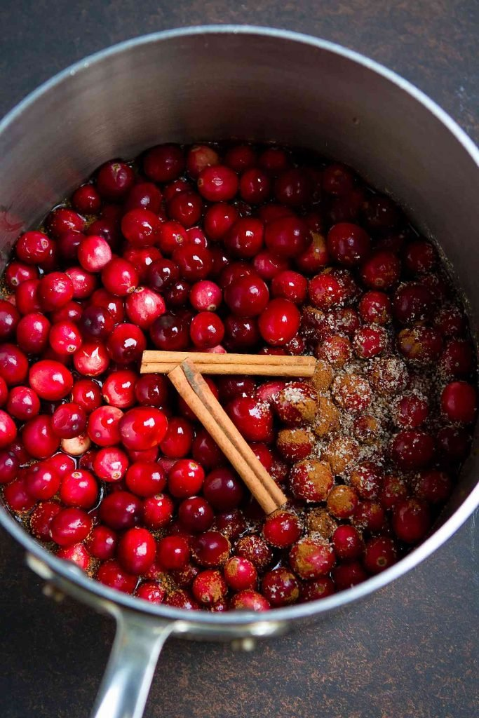 Cranberries, cinnamon sticks and nutmeg in a stainless steel saucepan.