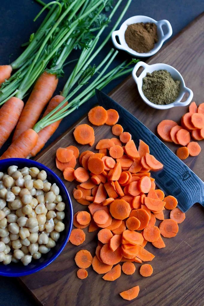 Chopped and whole carrots, spices and chickpeas on a wooden cutting board