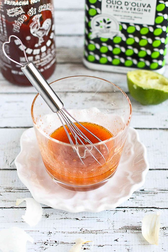 Sriracha lime vinaigrette in a glass with a whisk
