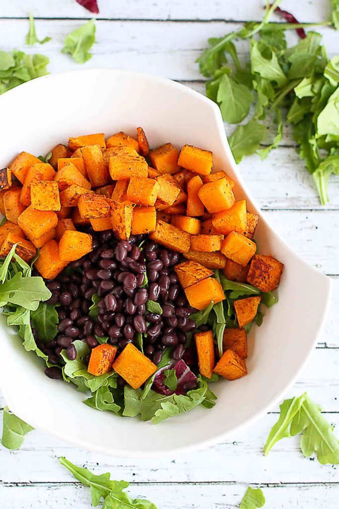Roasted squash, black beans and arugula in a large white bowl.
