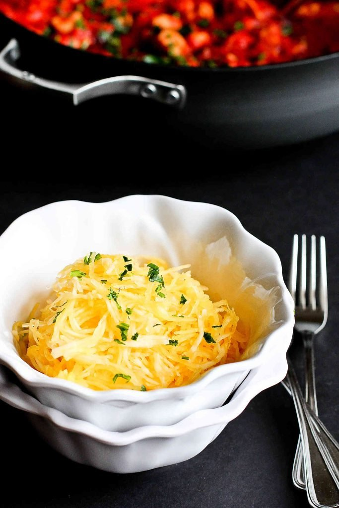 Shredded spaghetti squash in a white bowl, with fork son the side.