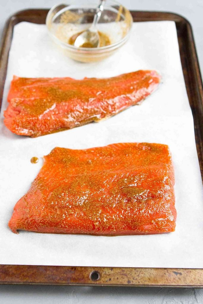 Spice-rubbed salmon fillets on a parchment-lined baking sheet.