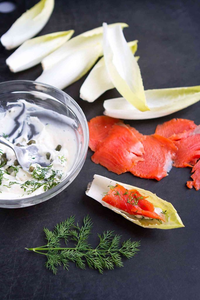 Endive leaves, bowl of cream cheese and smoked salmon on a black cutting board.